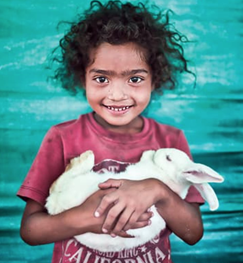 Girl holding a white rabbit in her arms.