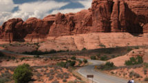 Motorcycle driving past Courthouse formation at Arches National Park, Utah