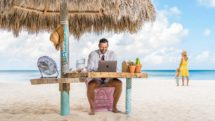 Dad working from beach palapa at Boardwalk Boutique Hotel Aruba on Palm Beach.