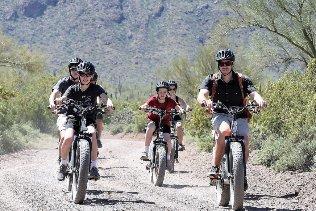 Family on fat tire mountain bikes explores the arid trails at White Stallion Guest Ranch.