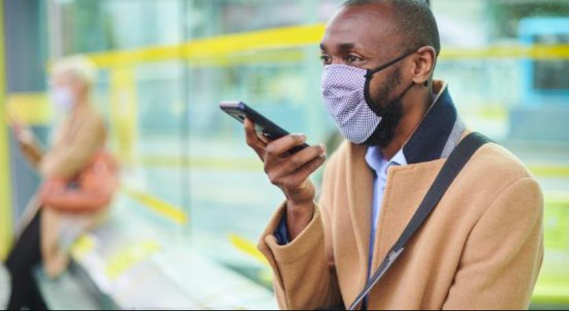 Man wearing mask talks into cellphone.