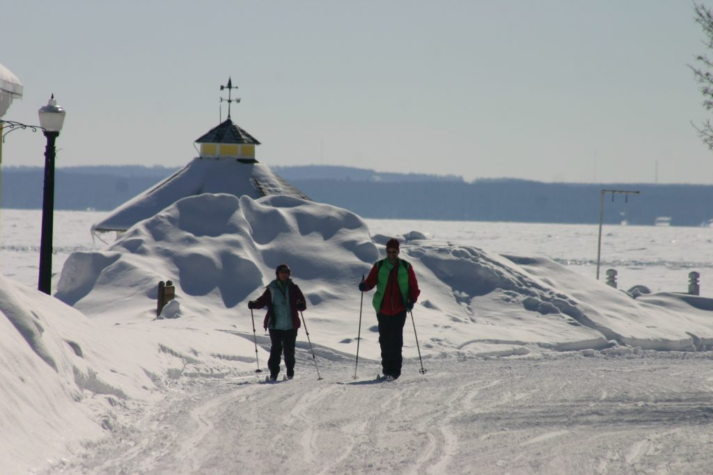Couples on cross country skis glide past steeple of Mackinac Island church.
