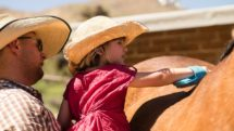 Cowboy holds up a girl so she can groom her horse at Elkhorn Ranch in Arizona.