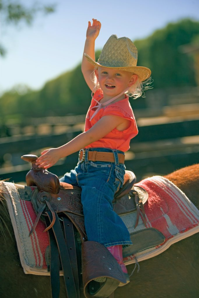 Young girl sits on top of a horse and waves like a bronco rider.