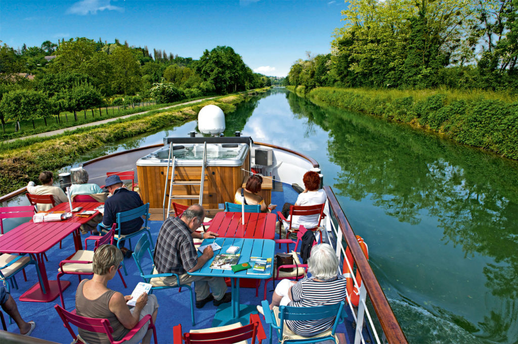 Relaxing on the top deck of a barge cruising a French canal.