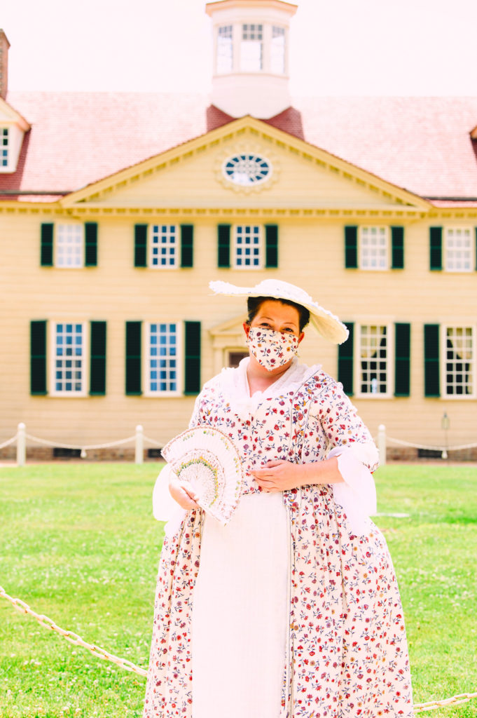 Mount Vernon re-enactor in costume and face mask.