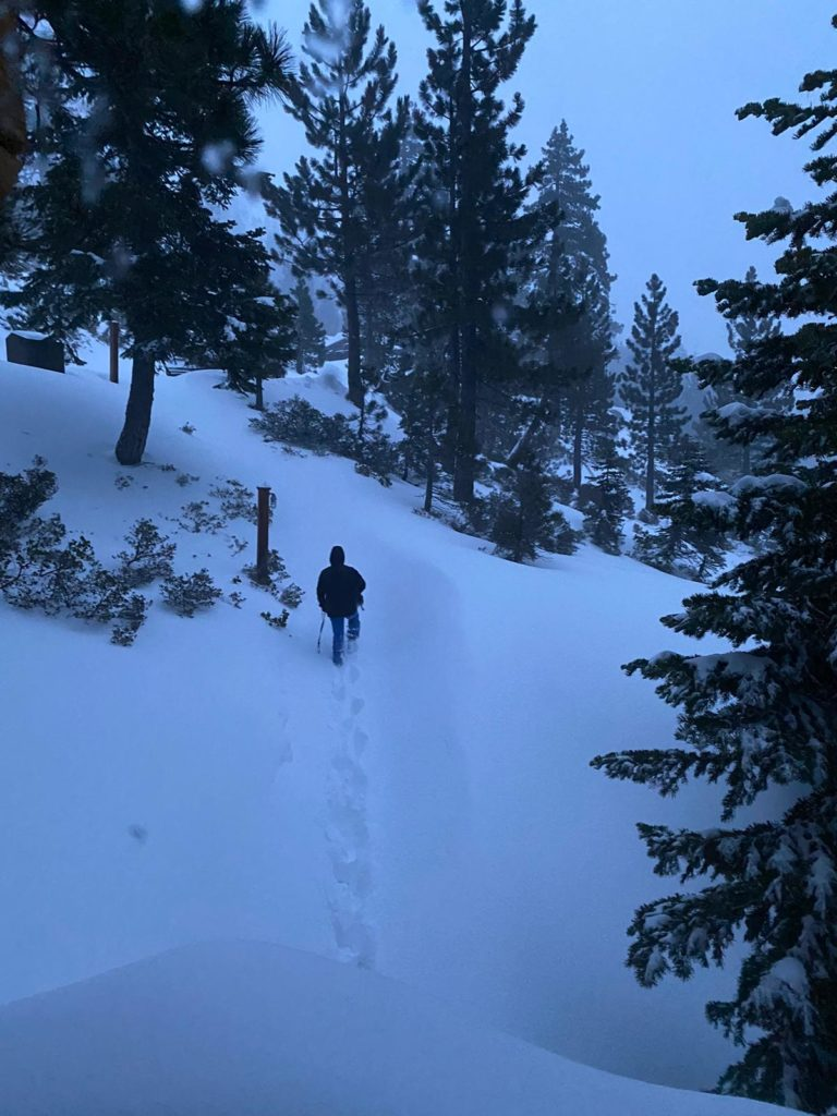 Man hikes through deep snow by himself in the backcountry of Alpine Meadows at Lake Tahoe.