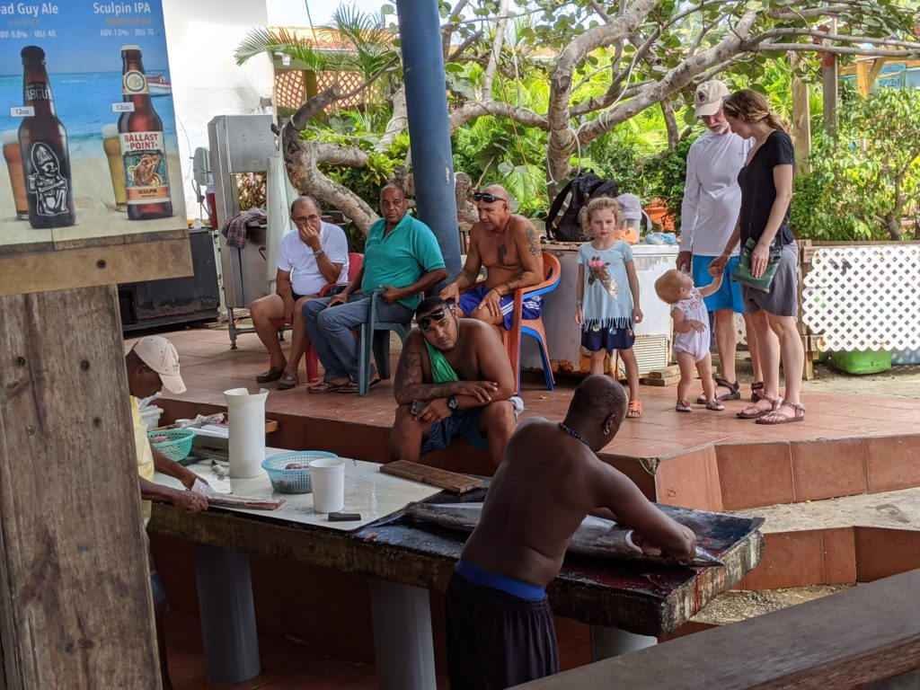 Family watches as local men clean fish at Zeerovers Cafe on Aruba.