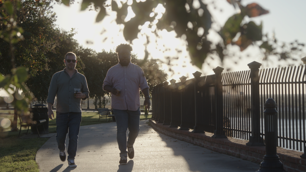 Two men walking along the Natchez waterfront.