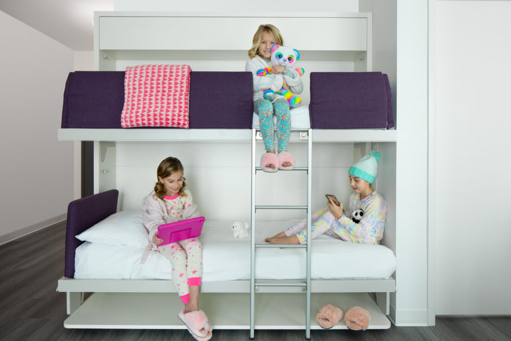 Three girls sit on bunk beds in their room at YotelPAD Park City in Utah.