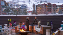 Two families sit in front of a firepit on the patio of YotelPAD Park City in Utah.