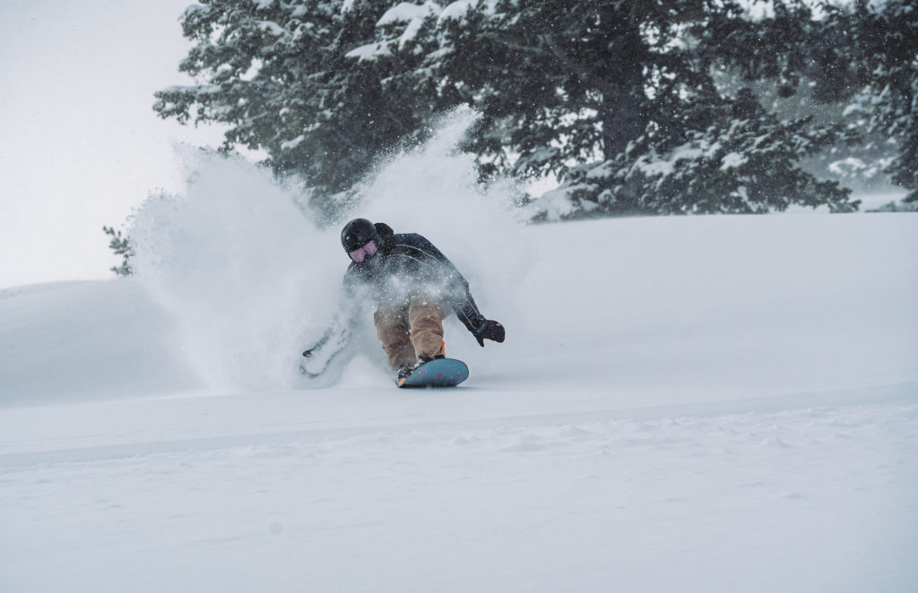 Snowboarder at Snow Basin in deep powder, photo by Brooks Roe for Snowbasin.