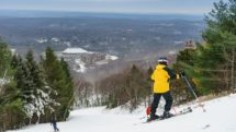 Skier looking down the slopes at base village of Camelback Resort in the Poconos.