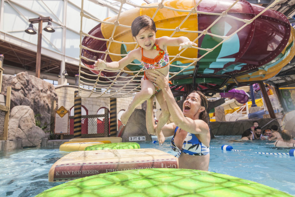 Girl being carried over rafts by mom in a pool at Aquatopis Waterpark at Camelback Resort.