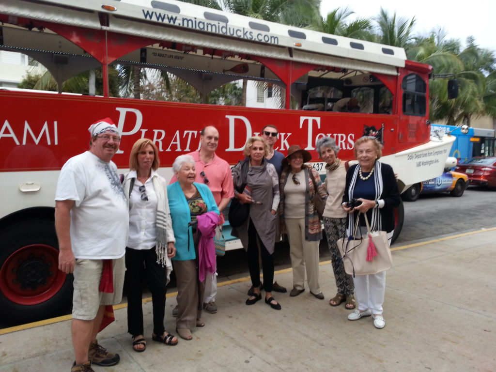 Group posing with guide in front of Miami Pirate Duck tours amphibious vehicle.
