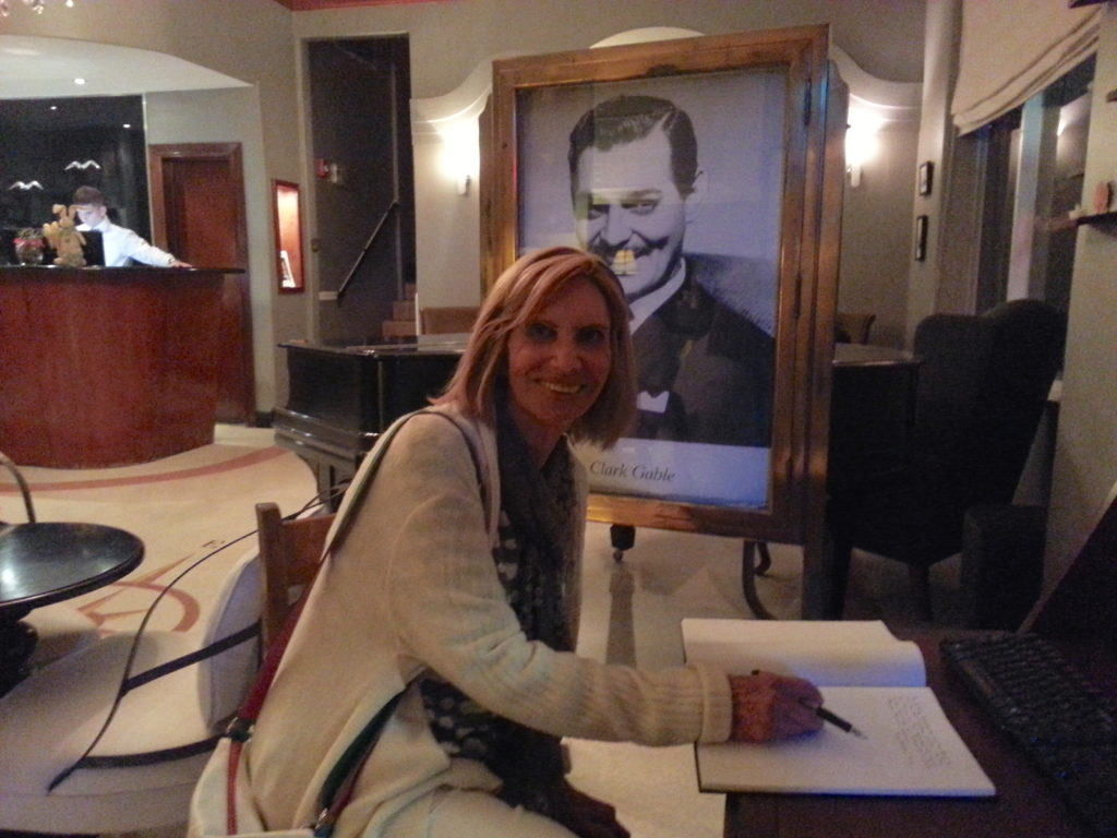 woman poses in front of Clark Gable picture at Cadet Hotel Lobby, Miami Beach.