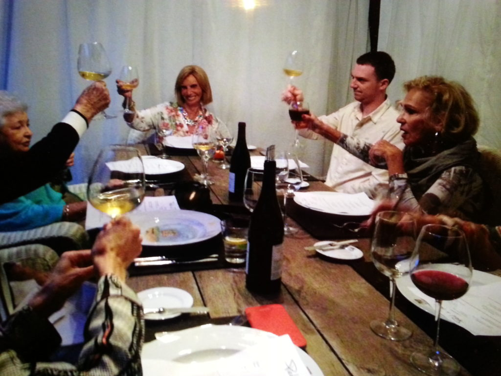Festive group toasting with wine at a dinner table.