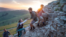 Parents and kids are scrambling over rocks on summer hike in Vail Valley.