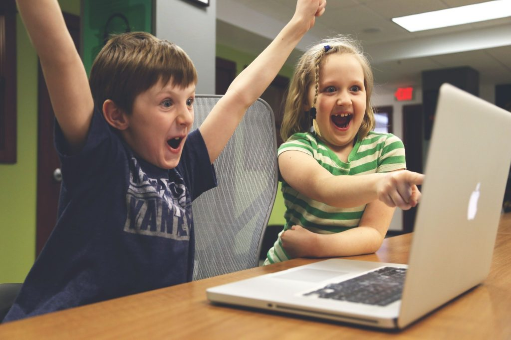 Two kids playing on a laptop are cheering at what they see.