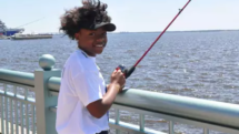 Girl with fishing rod on a pier with Kids Fish Camp