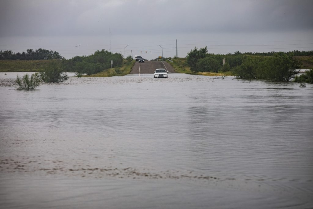 Single car stuck on flooded street after hurricane.