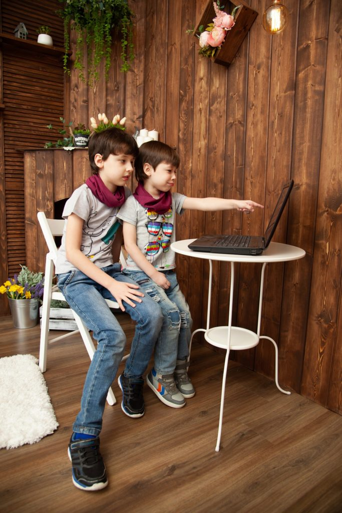 Two boys share a laptop at a table in a wood panelled room.