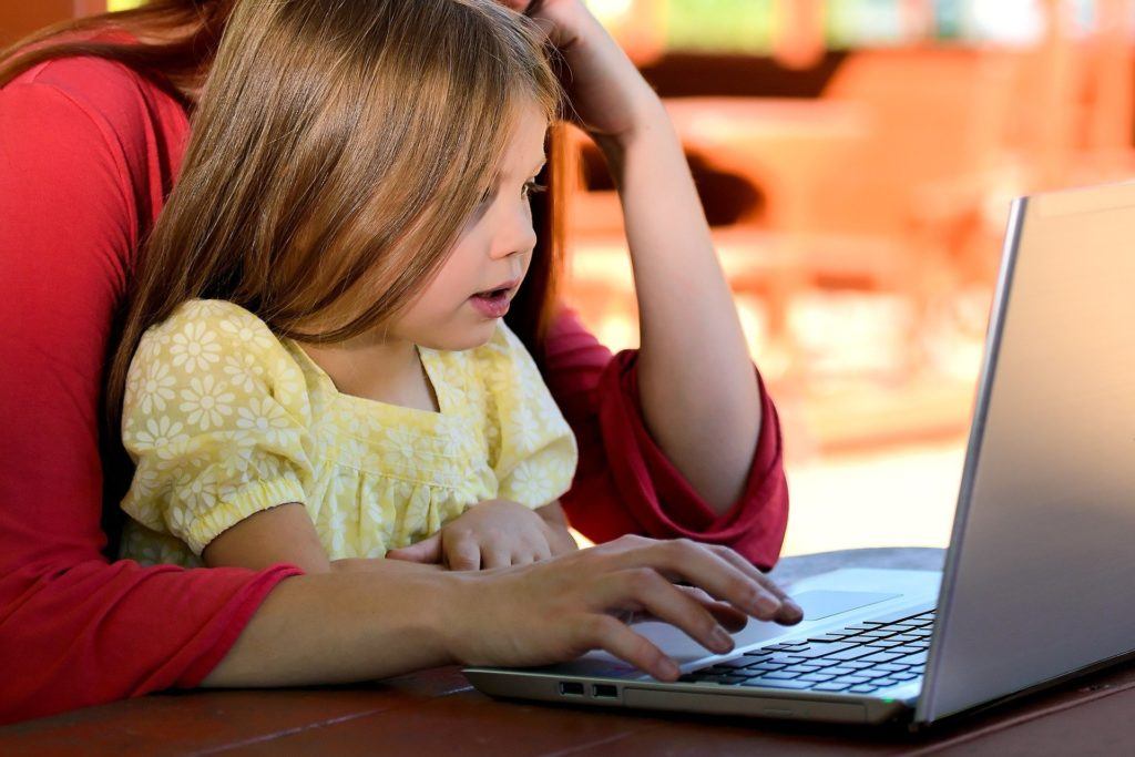 Mom sits at laptop computer with young girl on her lap.