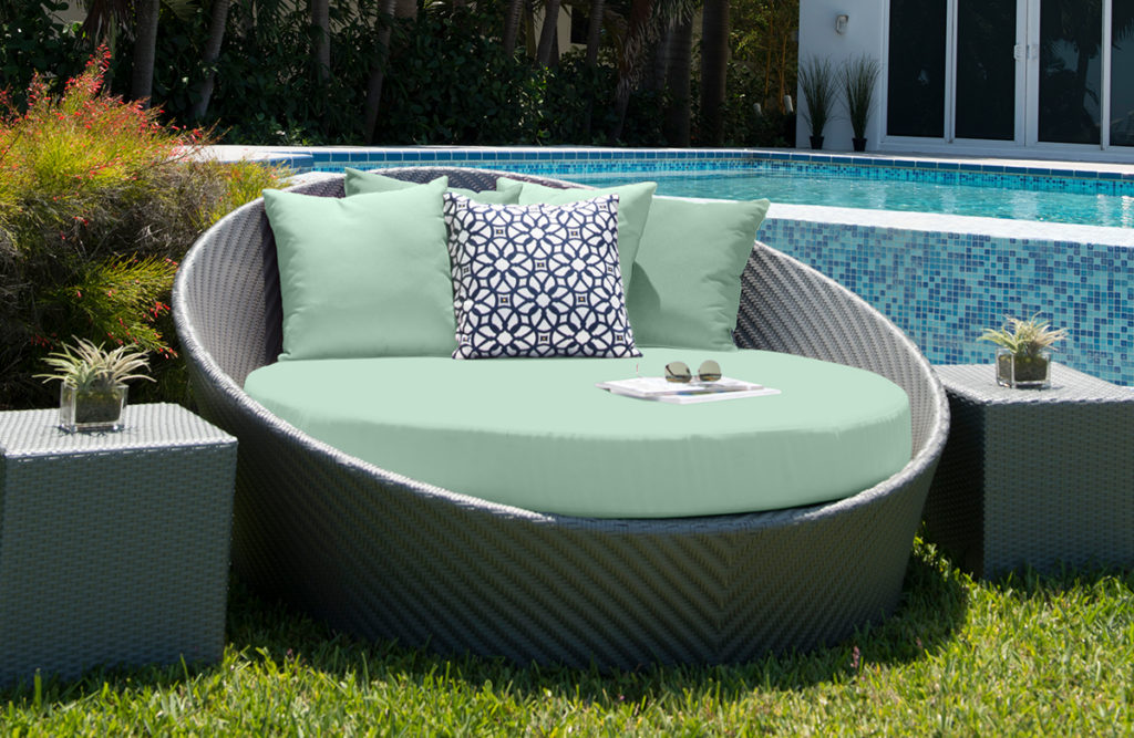 Pale green daybed on lawn in front of pool.
