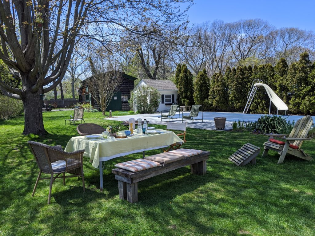 Long Island home with a backyard dining setup that resembles a Tuscan farmhouse