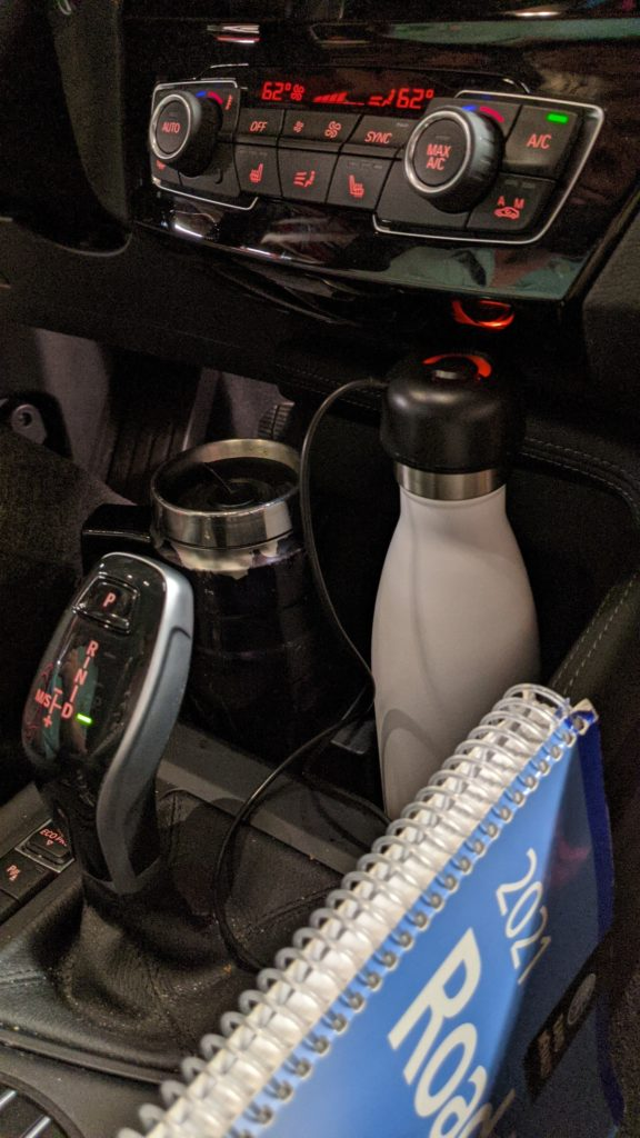 Car dashboard with travel coffee mug and water bottle plugged into charger.