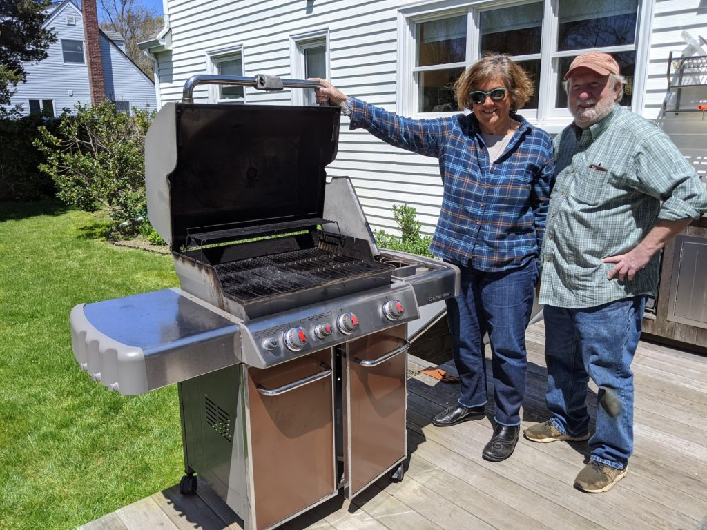 Couple standing next to a large Weber propane barbecue with burners.