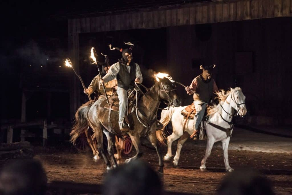 Riders on horseback carrying torches for the Shpeherd of the Hills outdoor drama.