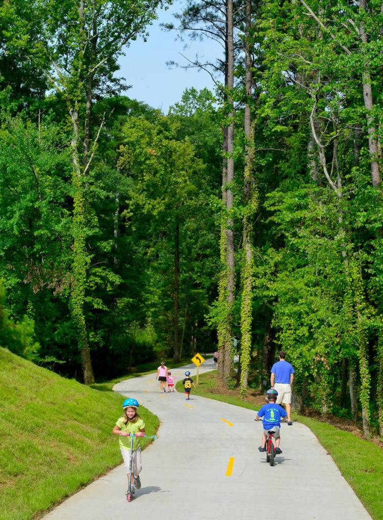 Kids on scooters and bikes in Brook Run Park, Dunwoody, Georgia