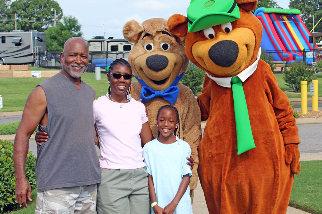 Yogi Bear characters greet Black family at a Jellystone Camp-Resort in the US.