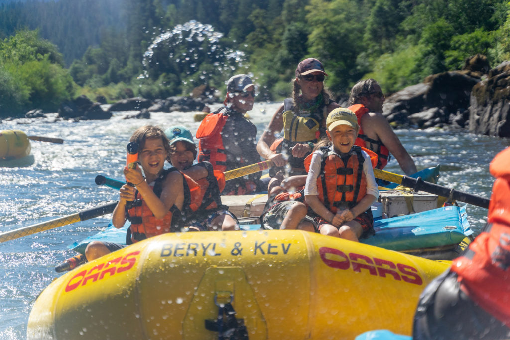 Family and guide on a river raft paddle along and play with waterguns.