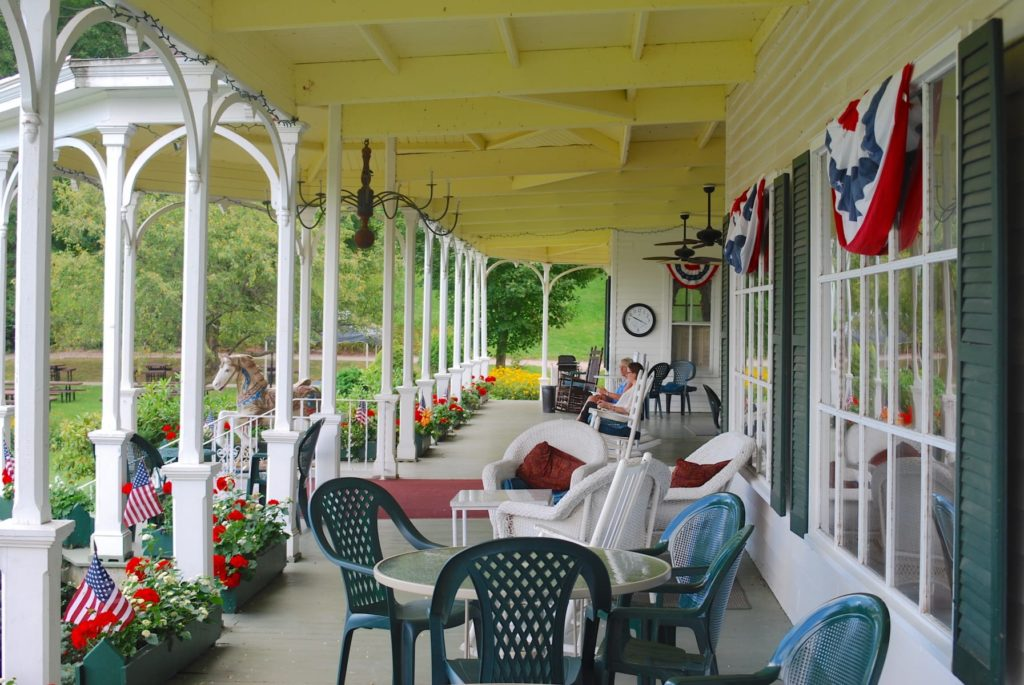 Victorian porch with tables and chairs, overlooking a lawn in the Catskills.