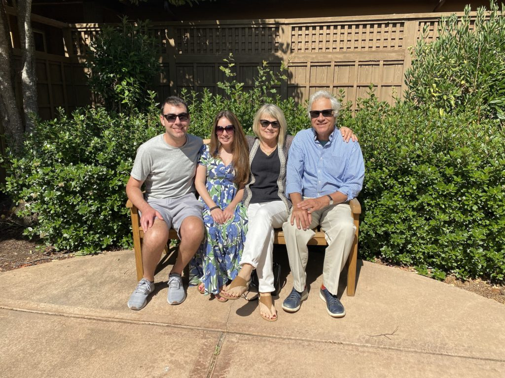 Adult children and parents sit on a bench