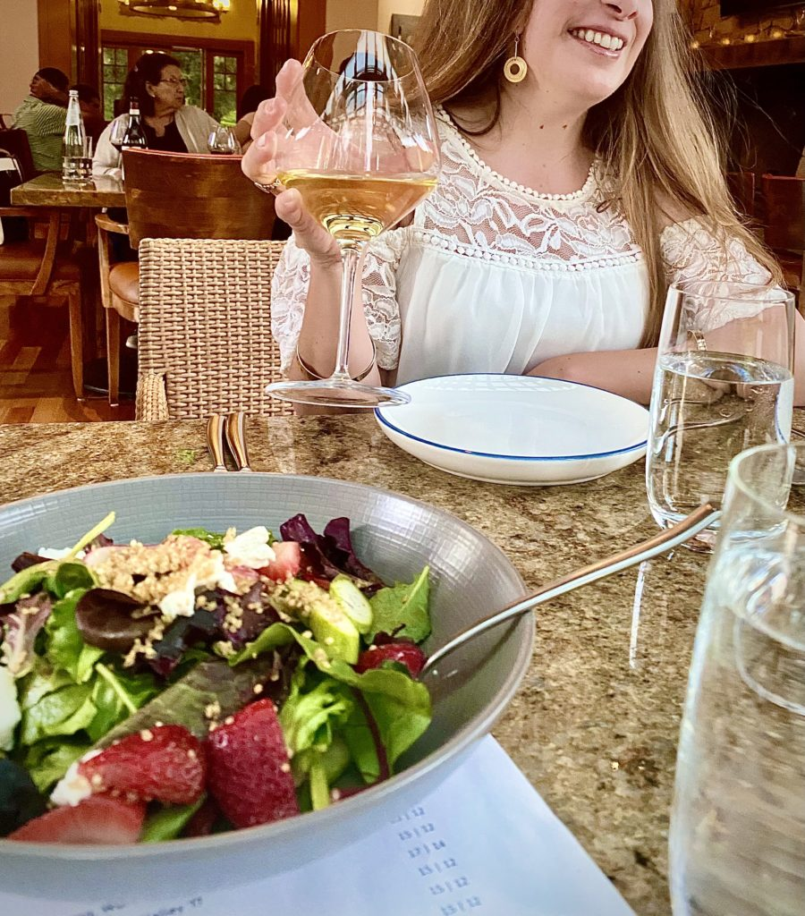 Woman drinking glass of wine at a dinner table with salad in the foreground.