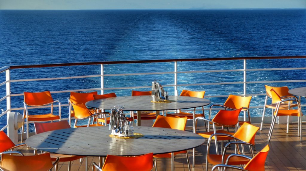 Back deck of a cruise ship set up with tables and chairs.