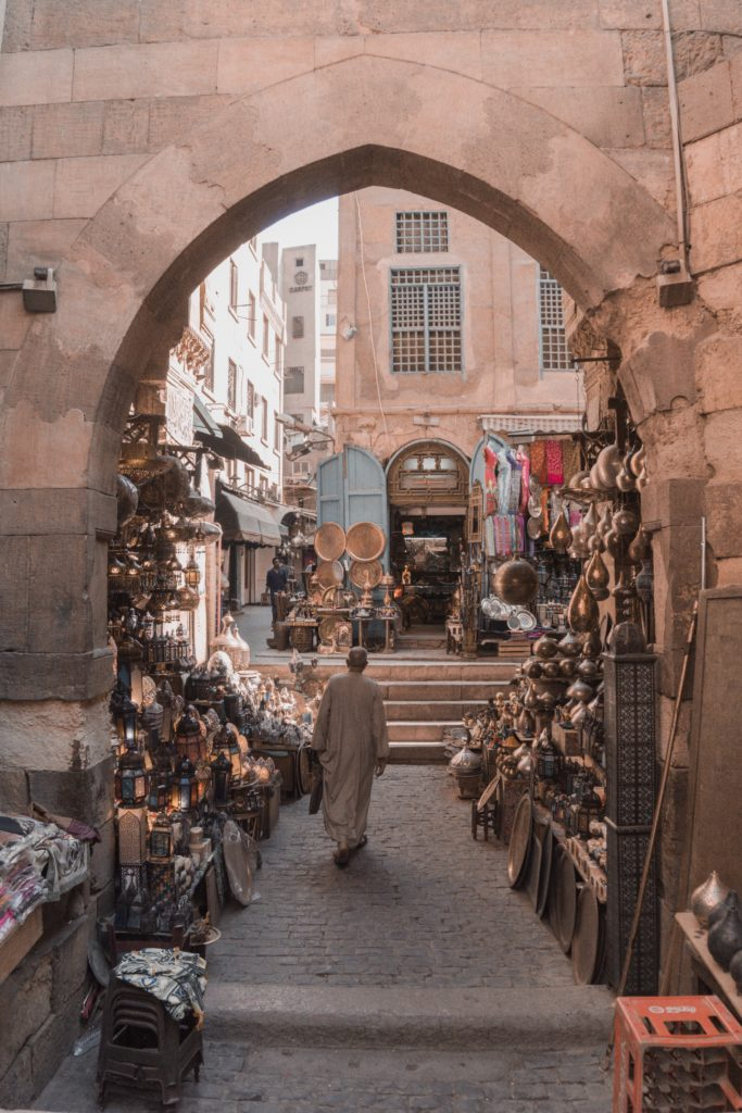 Man walks through the stall of a copper vendor in the Cairo souk.
