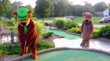 People in Yogi Bear and Boo-Boo Bear suits play miniature golf together at a Jellystone Park.