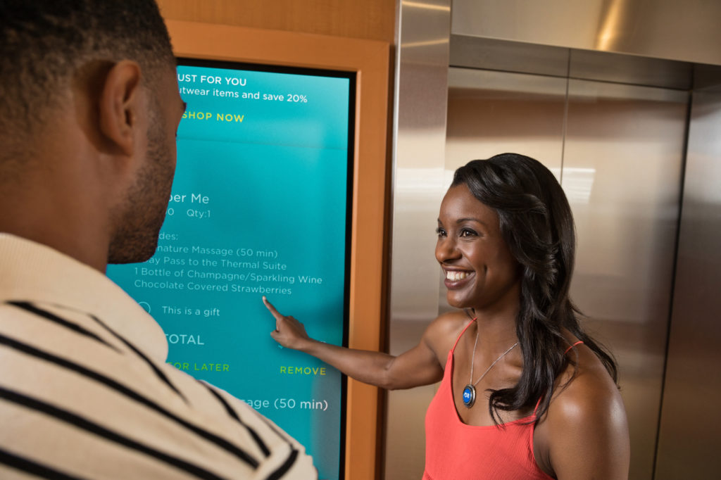 Man and woman look at an electronic board of shore excursions aboard a Princess cruise ship.