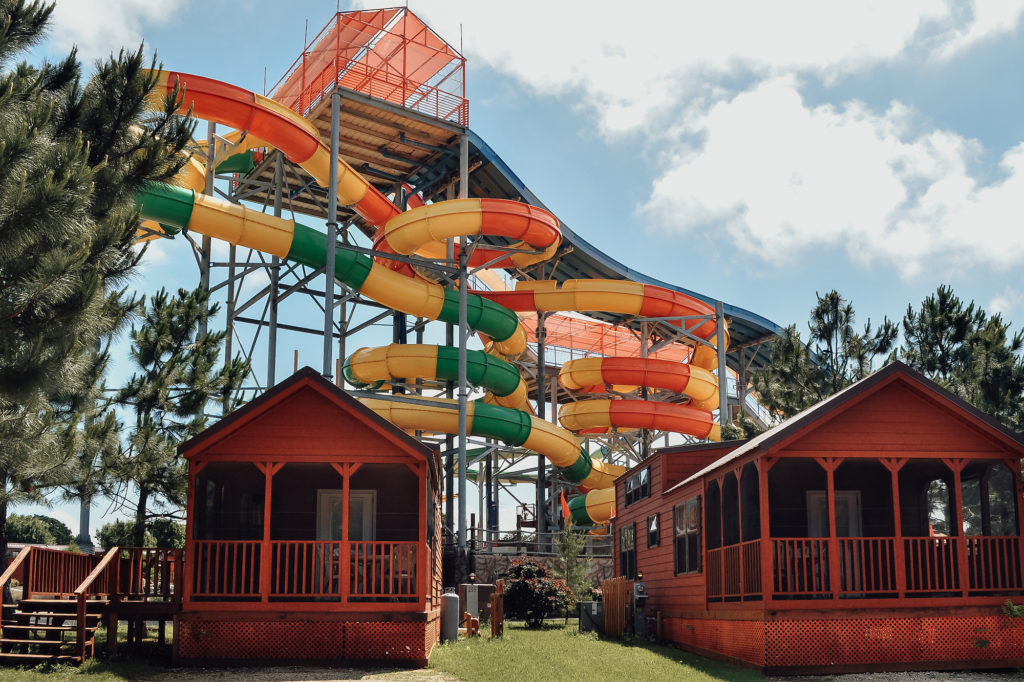 Rustic cabins and a large waterslide at Jellystone Park Camp-Resort in Burleson, Texas