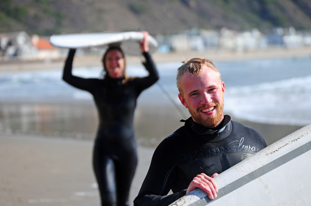 woman and man in wetsuits carry surfboards on the beach
