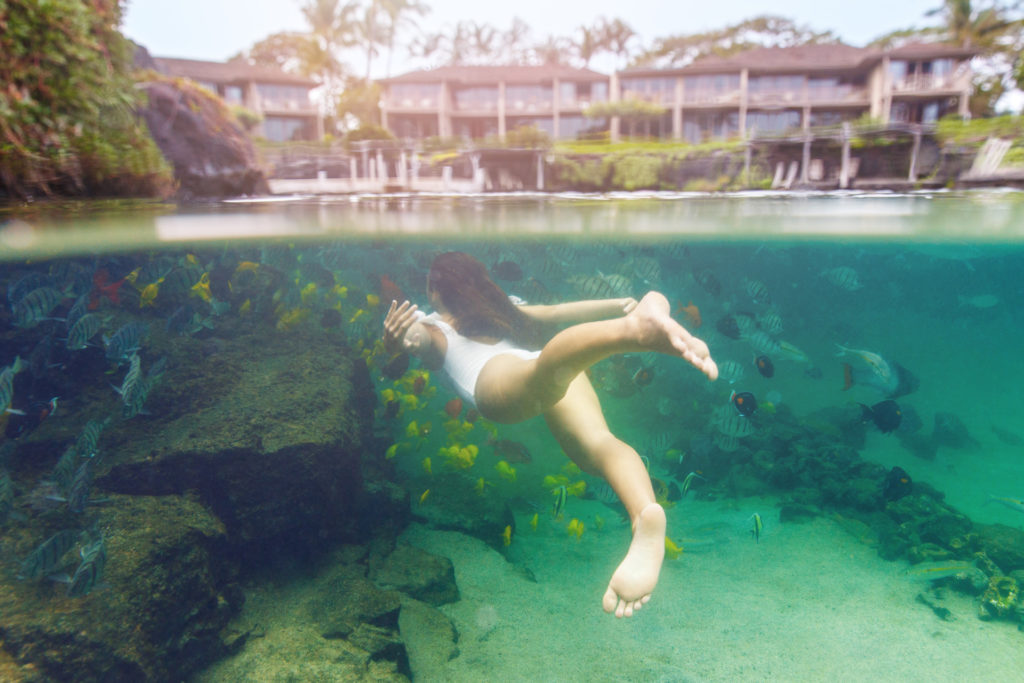 woman in white bathing suit swimming underwater with fish near a resort.