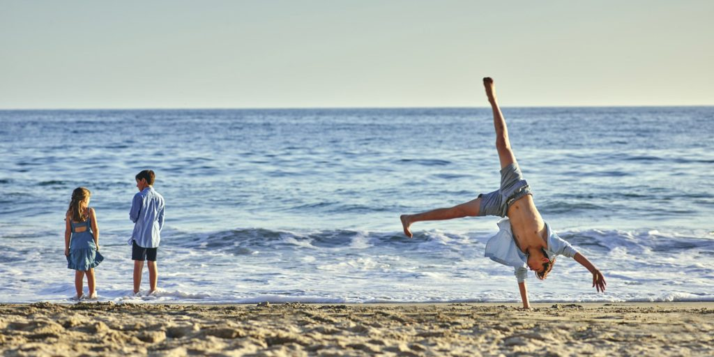 Kids stand at water's edge while a man does cartwheels on beach.