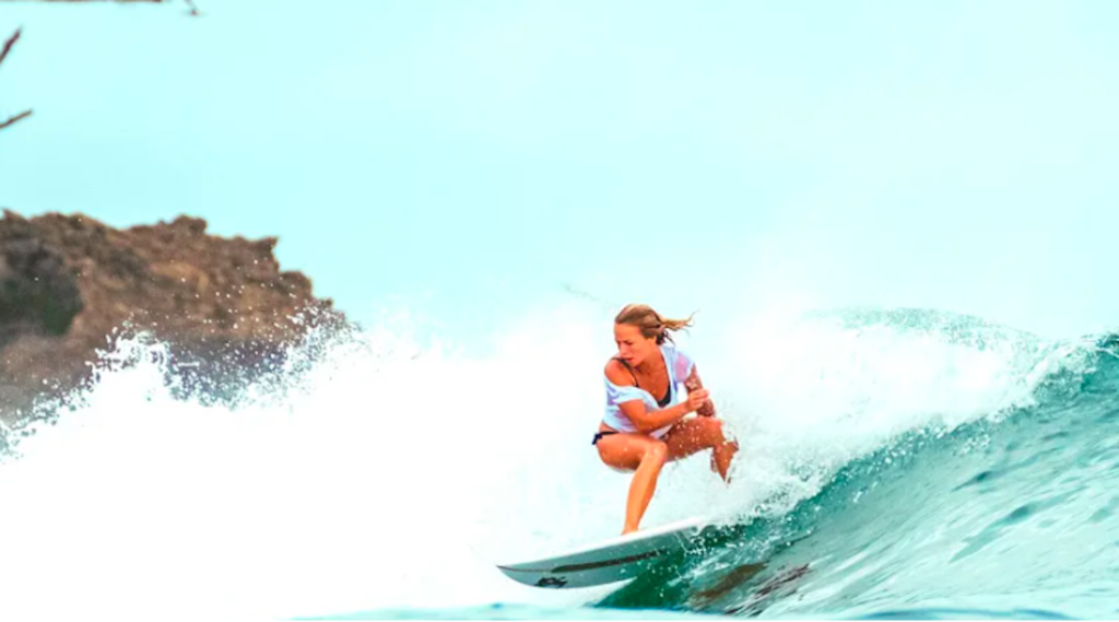 Woman surfing a large wave in Hawaii.