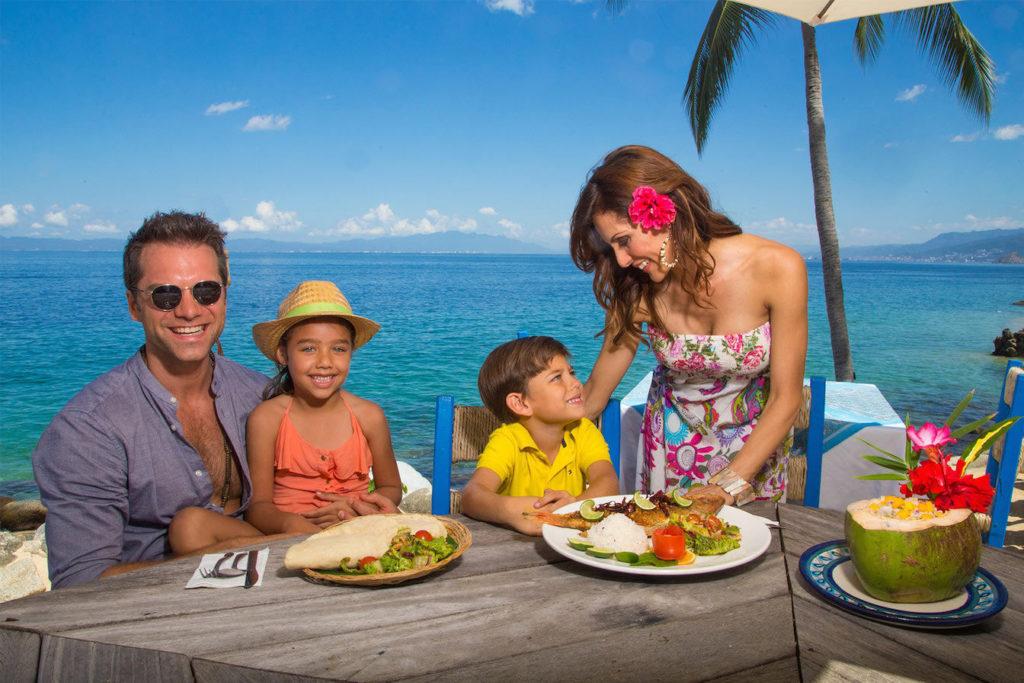 Family enjoying fish tacos at the beach in Puerto Vallarta.