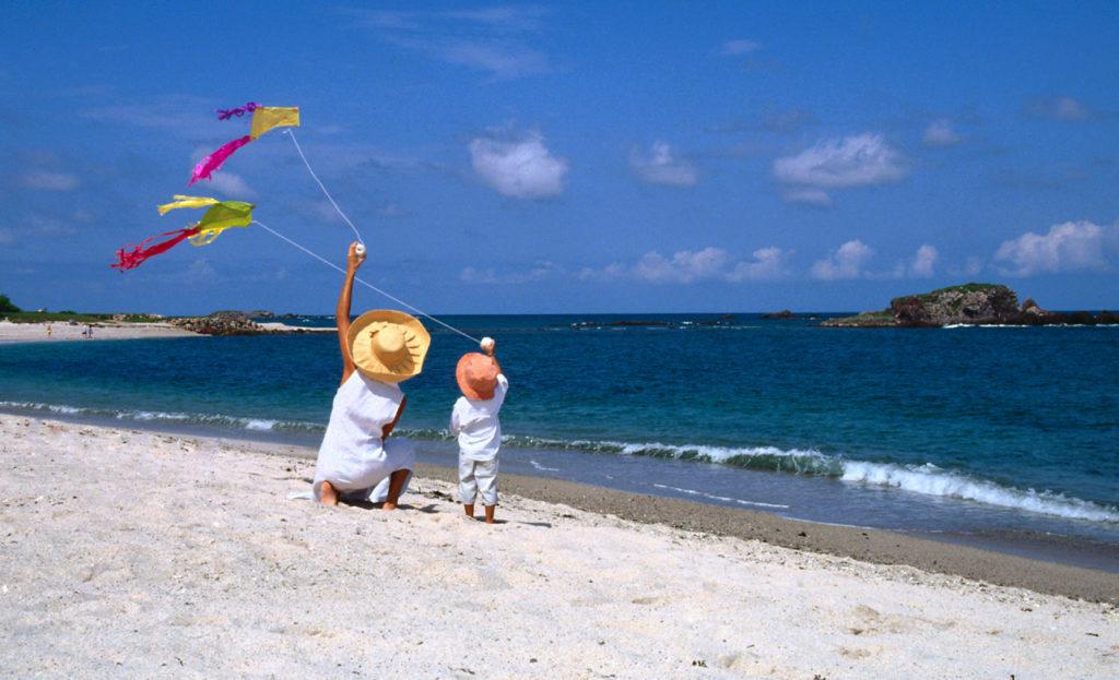 Family flying kites at the beach in Puerto Vallarta.
