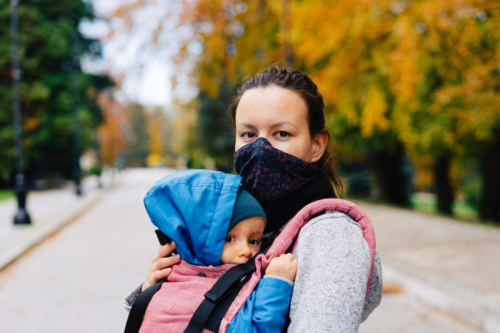 Mom in face mask holds baby